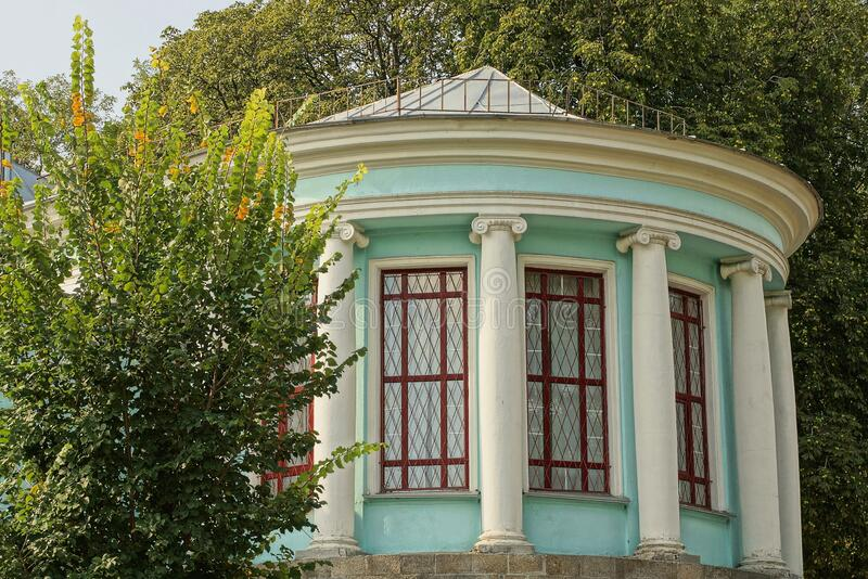 Old round historical building with white columns, a blue wall and large windows. Overgrown with green vegetation on the street royalty free stock photos