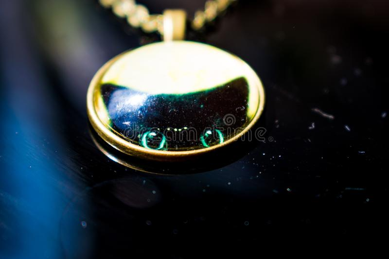 Old round pendant of Golden color with a convex image of a black cat. Like a talisman on a chain. On a black glossy background. royalty free stock photo