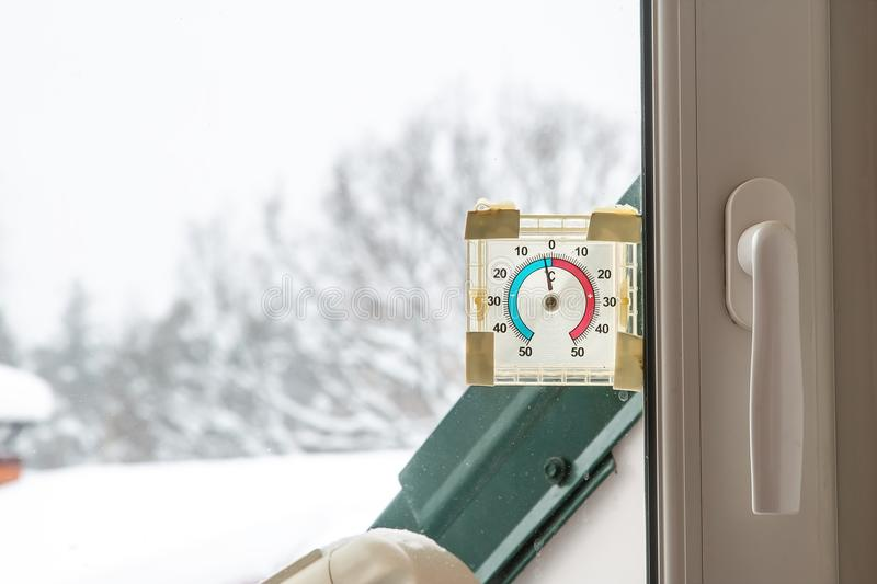 Old round plastic thermometer outside on the window. Shows minus four degrees on the street royalty free stock photography