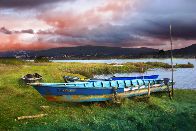 Old Row Boats. Rural landscape with old row boats in the river shore stock photo