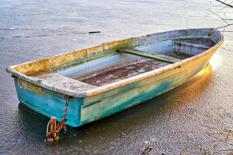 Old rowboat on a frozen lake in winter stock photos