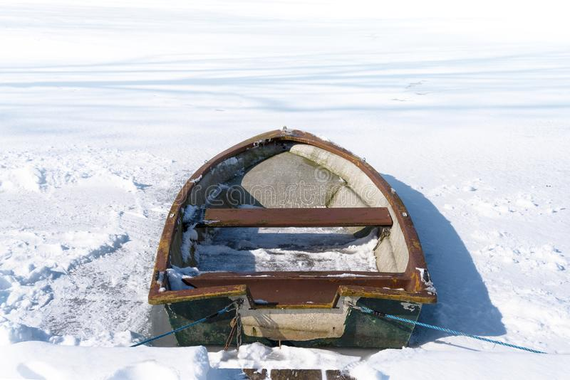 Old rowing boat in the frozen lake on a sunny winter day, concept metaphor for burn out, slow down and standstill in the business stock photo
