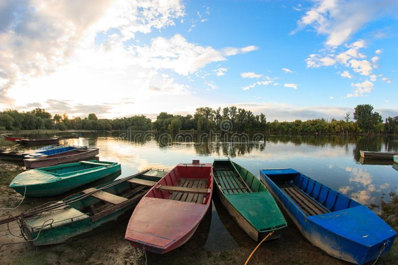 Old rowing boats along the lake shore or river bank in early morning stock photography
