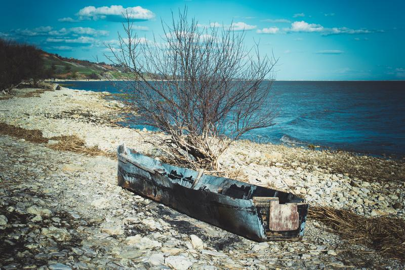 Old ruined boat on the beach. Abandoned fishing boat stock image