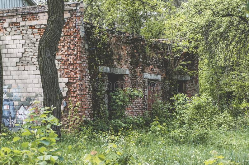 Old ruined creepy scary house at the abandoned summer kids camp. Old ruined scary creepy house in the forest at the abandoned summer kids camp royalty free stock photography