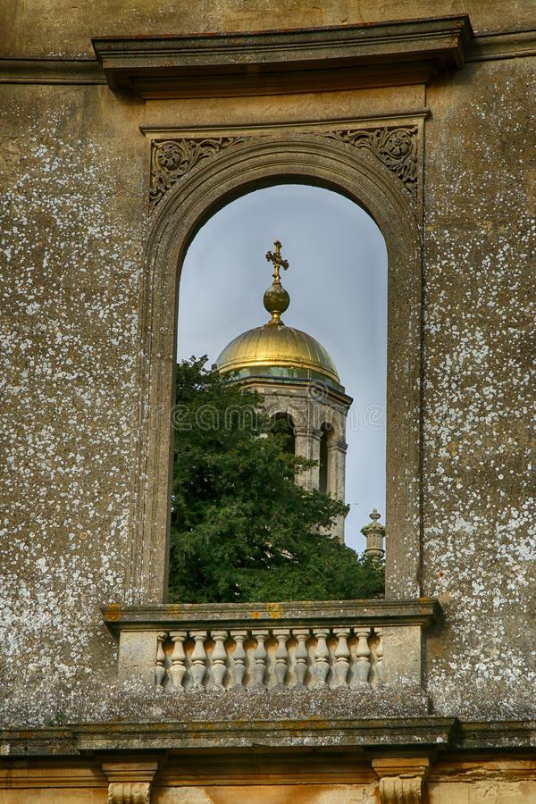 Old ruined domed window with gold domed church wrest park, west midlands. Ruined decorative domed window with gold domed church in the background ,wrest park royalty free stock photography