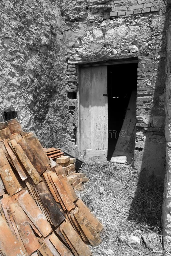 Old ruined shack. Ruined door of an old shack with in foreground some roofing-tiles royalty free stock photo