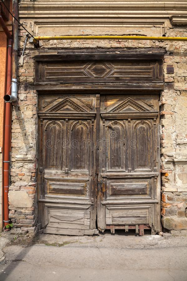 Old ruined wooden door. Decorated with beautiful carvings royalty free stock photo