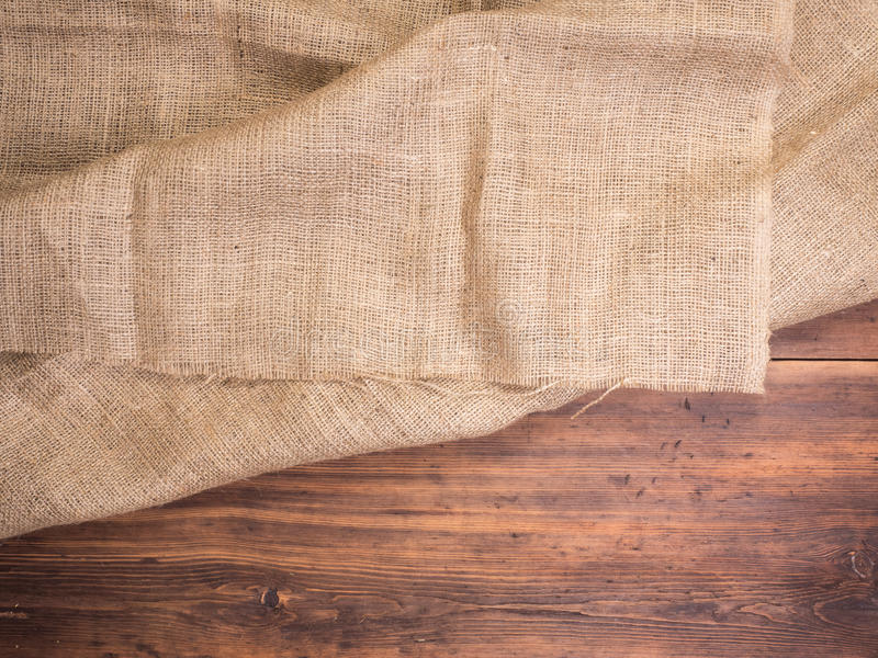Old rural wooden table boards and burlap vintage background, photo top view. Hessian, sacking texture on wooden. Background for your design. Copy space for your royalty free stock photos