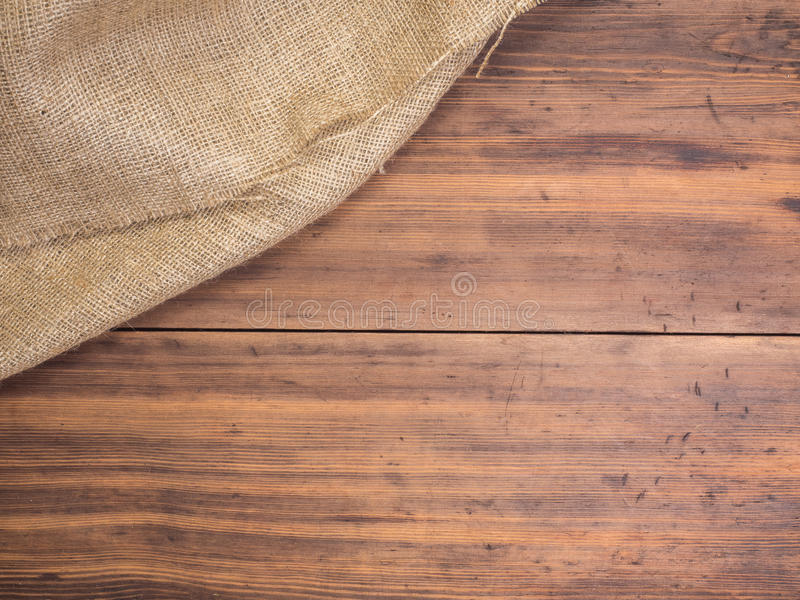 Old rural wooden table boards and burlap vintage background, photo top view. Hessian, sacking texture on wooden. Background for your design. Copy space for your stock photo