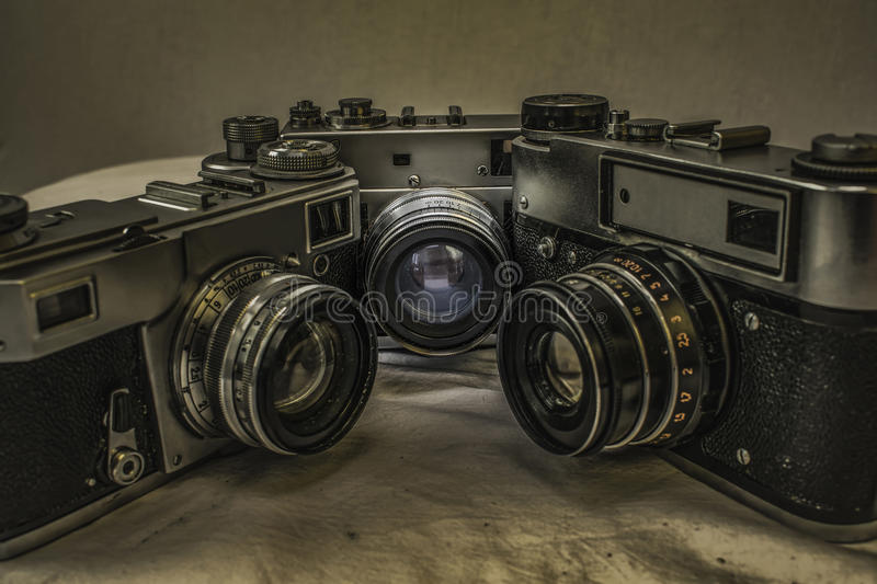 Old Russian analog film cameras with manual controls. Three old Russian analog film cameras on dirty canvas with vintage look. Cameras are arranged in a square royalty free stock image