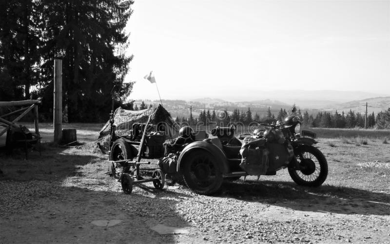 Old russian or german military bike. Picture of a motorcycle in the field with machine gun, rifle, trailer and old military tent from the time of the Second royalty free stock photography
