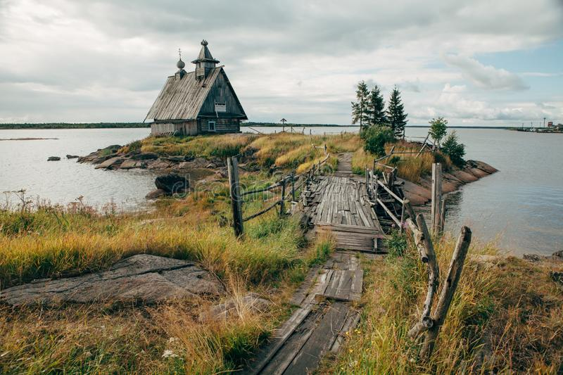 Old russian Orthodox wooden church in the village Rabocheostrovsk, Karelia. Abandoned church on the coastline. royalty free stock images