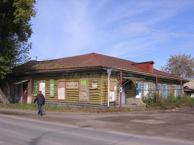 Old Russian village house of the Siberian hut past the street people passerby. Rural view stock photo