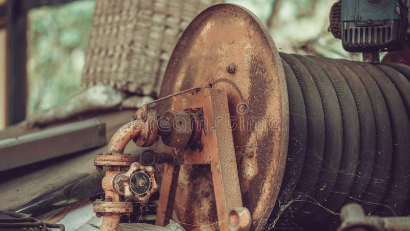 Old Rust Water Hose Reel Axis stock photo