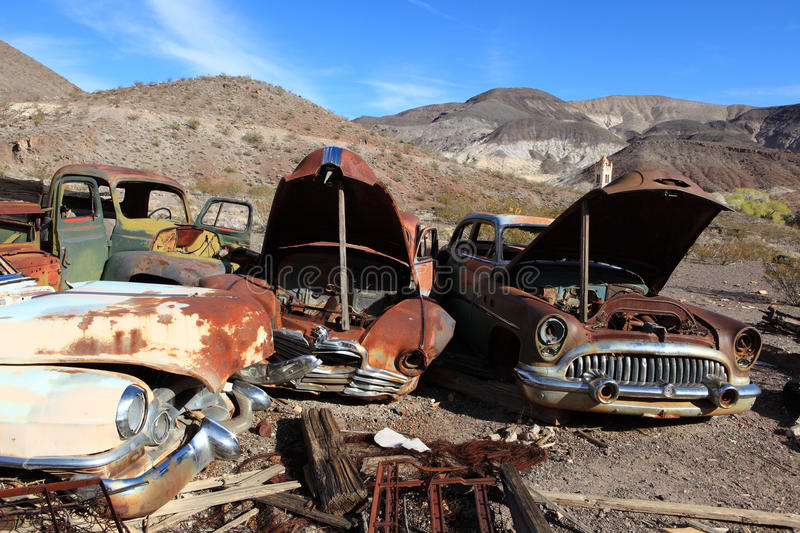 Old rusted cars in junk yard royalty free stock photo