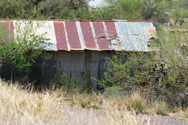 Old corrugated metal building in an overgrown yard. Old rusted corrugated metal building in an overgrown yard with trees royalty free stock images