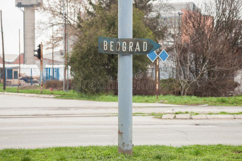 Old, rusted and in decay sign indicating the direction of Belgrade Beograd in Serbian in an abandoned industrial zone royalty free stock photos
