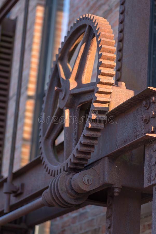 Old rusted industrial steel gear and beams outside in sunlight stock photography