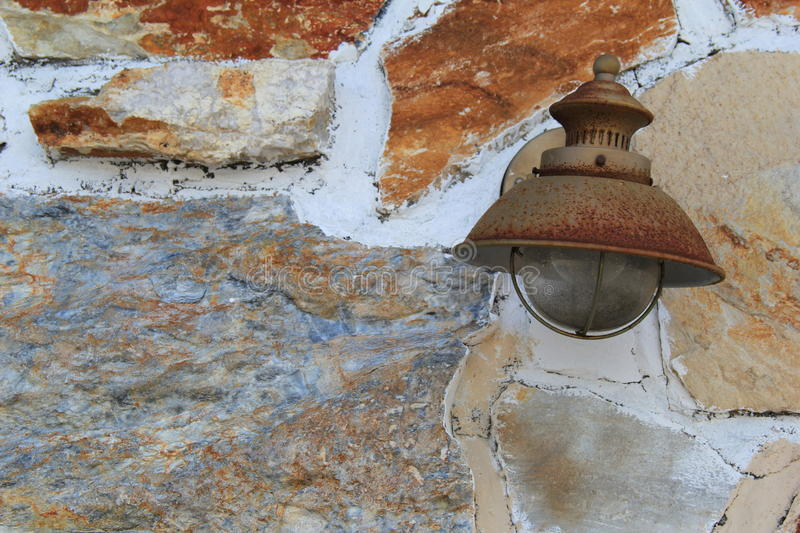 Old rusted lantern on colorful stonewall royalty free stock photos