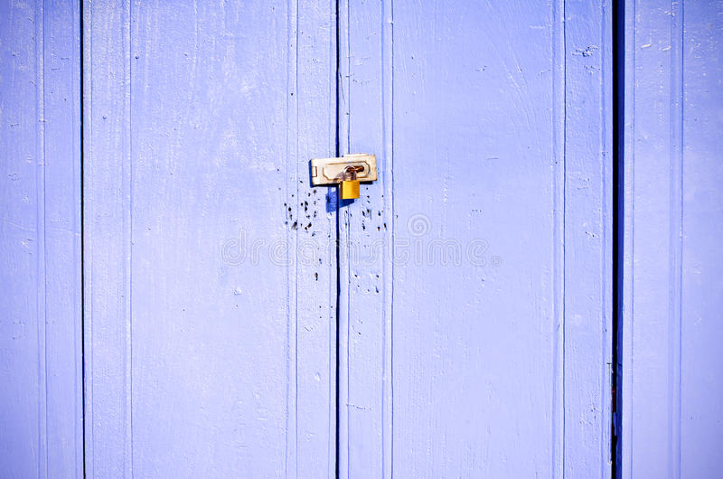 Old rusted lock on blue wooden doors stock photography