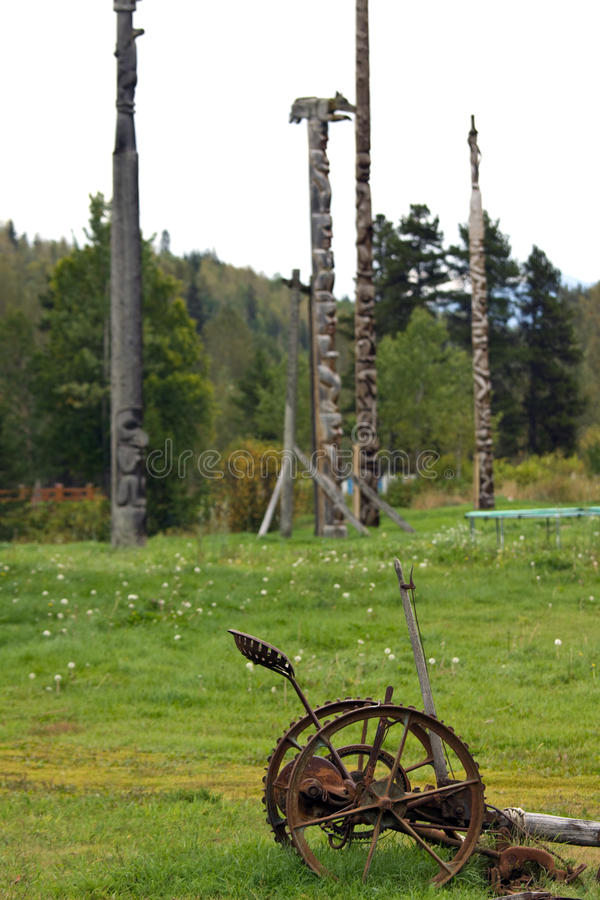 Old rusted out plow in front of traditional Gitxsan totem poles royalty free stock photography