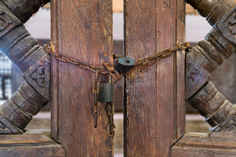 Old rusted padlocks and rusted chain on a wooden double door stock photography