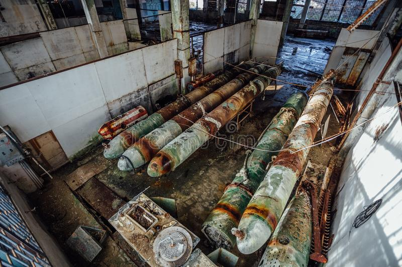 Old rusted submarine torpedoes in abandoned torpedo factory.  royalty free stock photos