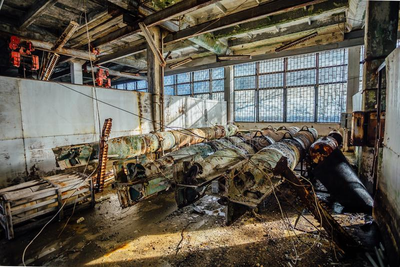 Old rusted submarine torpedoes in abandoned torpedo factory. Back view stock photo