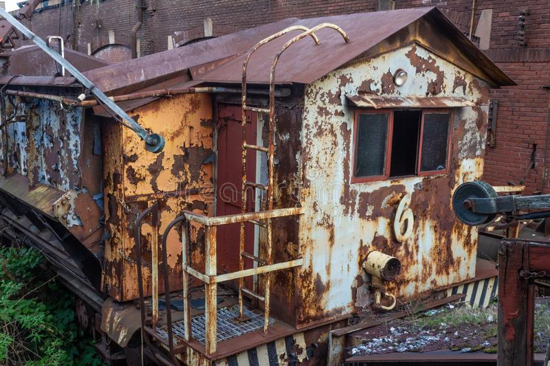 Old rusted train car beside a brick industrial building. Horizontal aspect royalty free stock photography