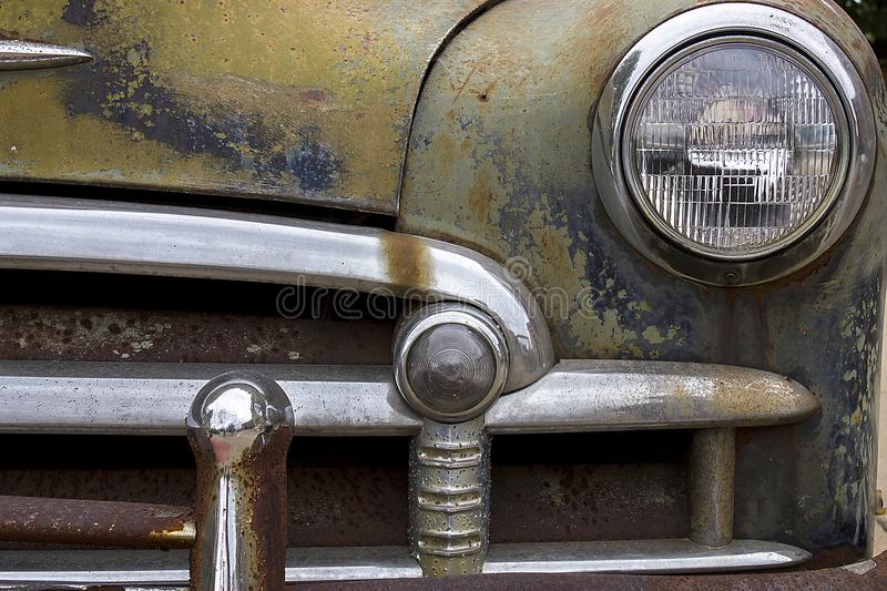 rusted chrome front bumper, headlight and grill of old junk car with peeling paint royalty free stock photo