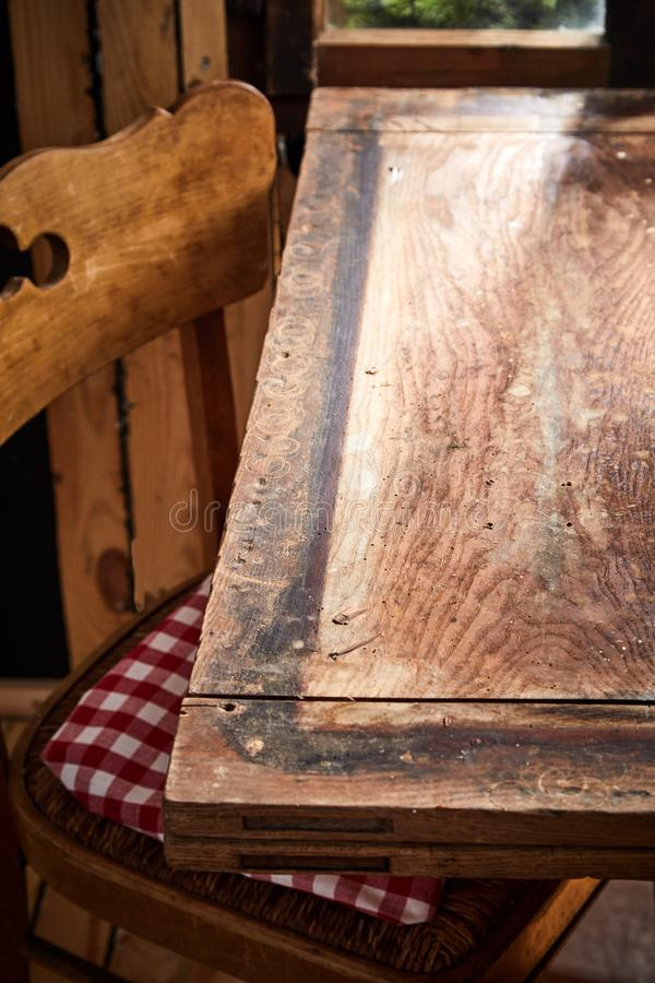 Old rustic bare empty table and chair. In front of a window in a tavern or pub with copy space for product or food placement in vertical format stock image