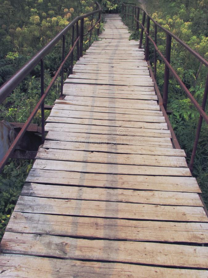 Old rustic bridge of wooden planks on a metal base with iron handrails, going into perspective stock photo