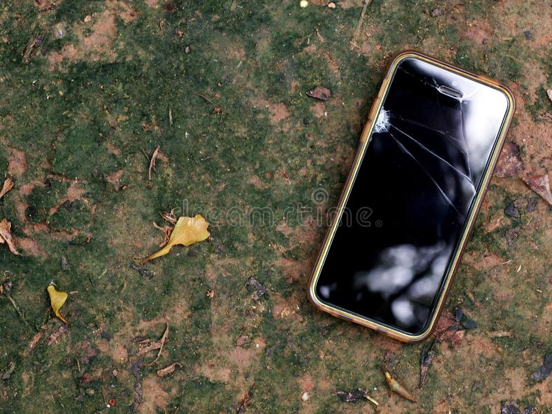 Old rustic broken smart phone in dirty silicone case laying on the floor stock photos