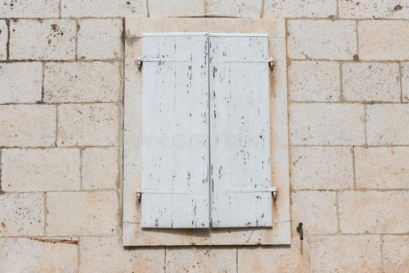Old rustic closed white wooden window shutters isolated on white background stock images