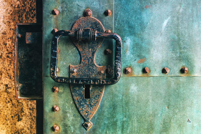 Old rustic copper castle metal door with large knocker royalty free stock images