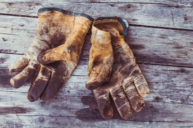 Top view of old rustic and dirty working gloves over wooden table,  gloves for each finger royalty free stock photography
