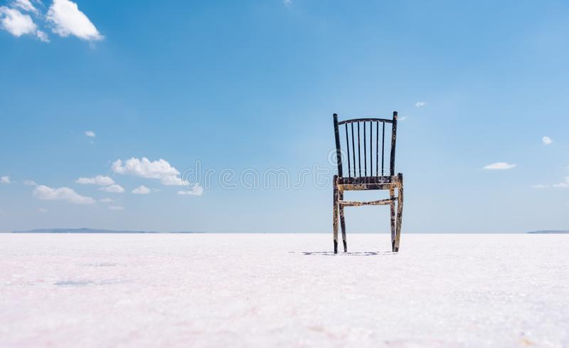 Old rustic empty chair at dry salt lake,. Minimalism concept royalty free stock photography