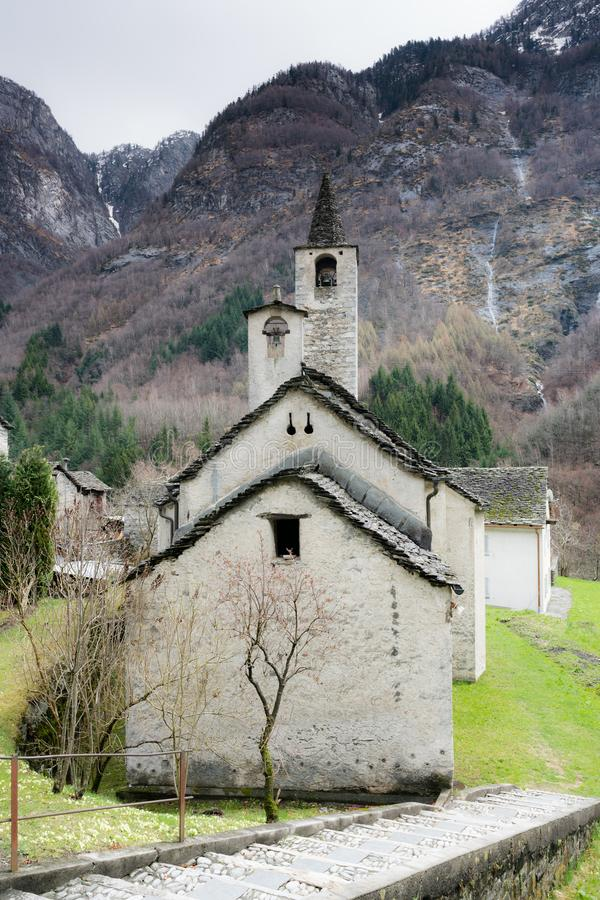 Old rustic historic stone church in a remote mountian valley in the Swiss Alps stock photos