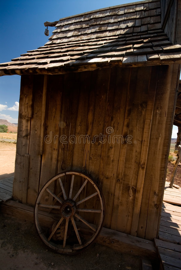 Old rustic shack. Old west style shack and old wagon wheel stock images
