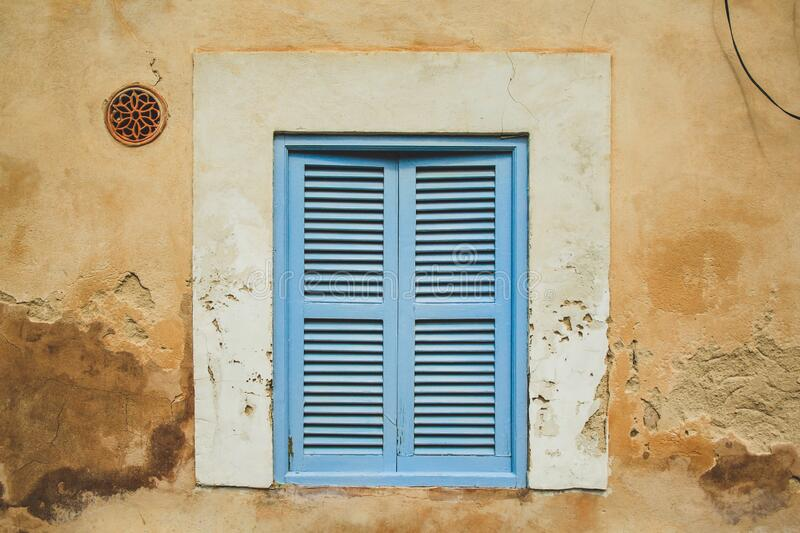 Old rustic window with grey closed shutters in Mallorca, Spain.  stock photo