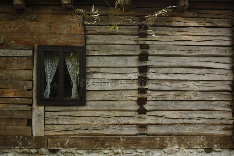 Old rustic wooden house with a window with white crocheted curtains. royalty free stock image