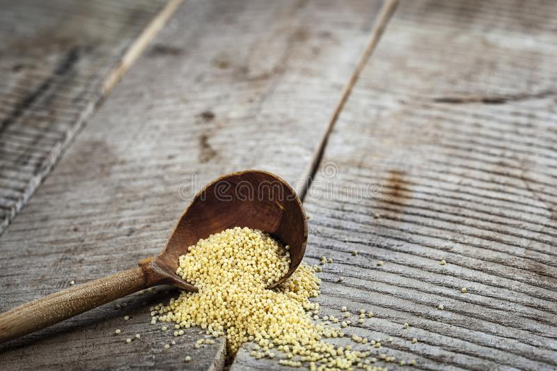 Old rustic wooden spoon with millet on wooden background. stock photo