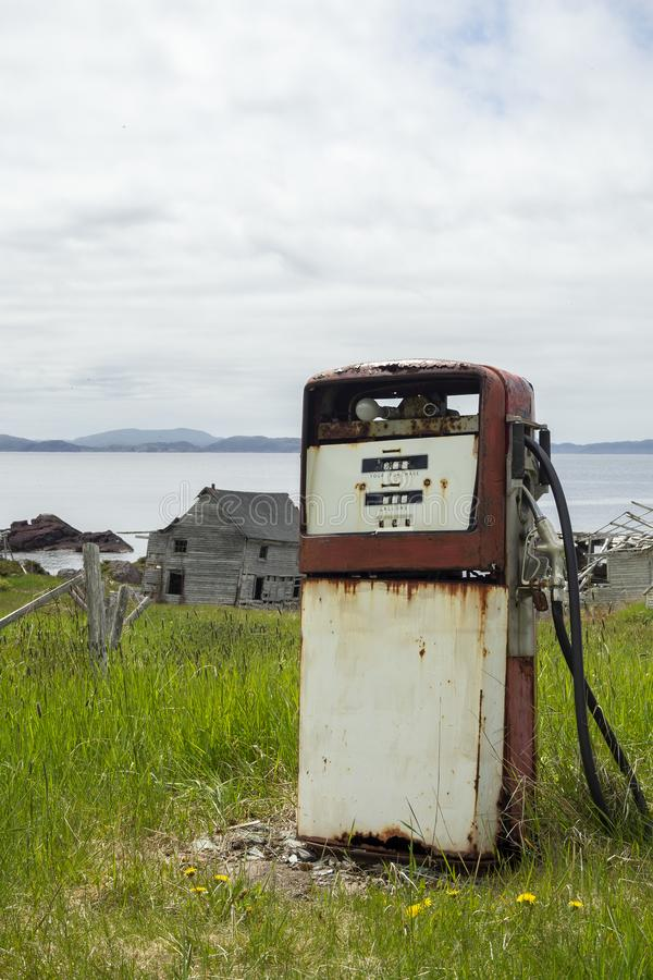 Old rusting gas pump. With adandoned building in the background symbolizing a dieing rural community royalty free stock photos