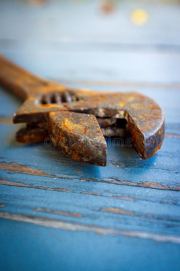 Old Rusty Adjustable Wrench. Contractors tool on worn wooden floor stock photo