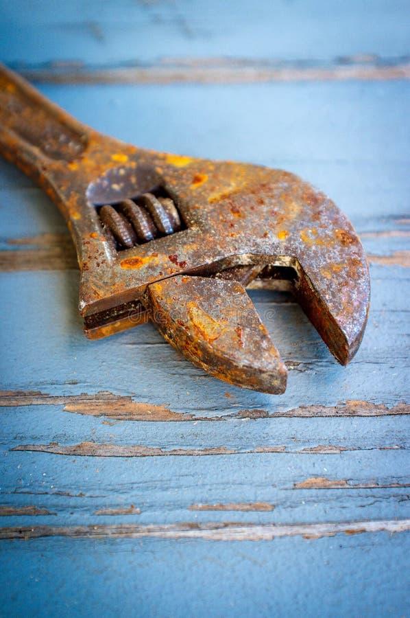 Old Rusty Adjustable Wrench. Contractors tool on worn wooden floor stock photos