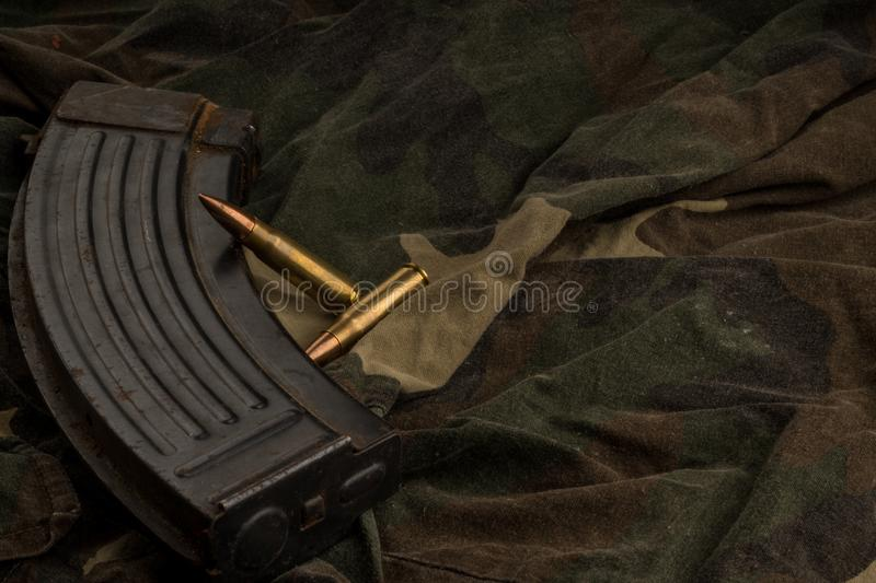 Rusty AK-47 magazine and bullets on camouflage textile background royalty free stock photography