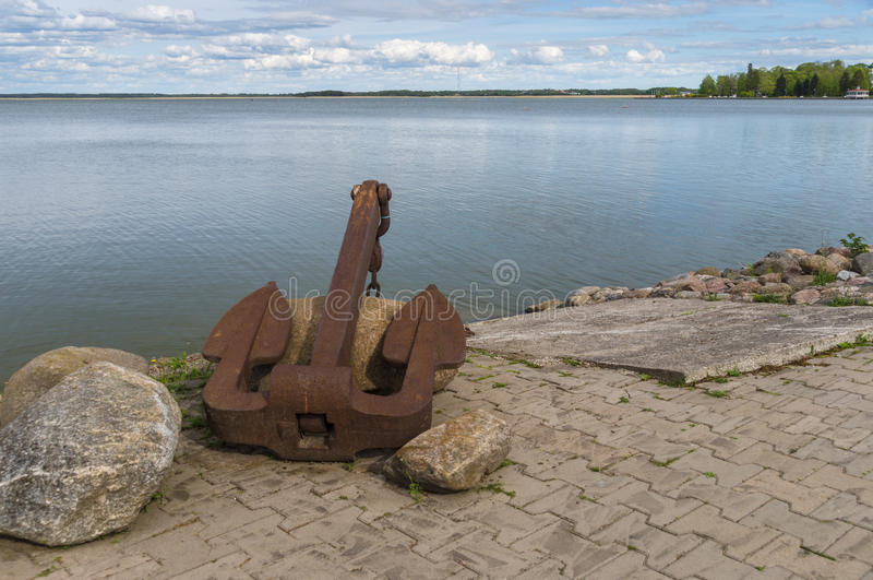 Old rusty anchor on sea coast royalty free stock photography