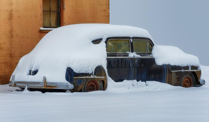 Abandoned snow covered rusted old car. A old rusty auto sets exposed through many seasonal elements. Snow layered will only add to it`s demise stock photography