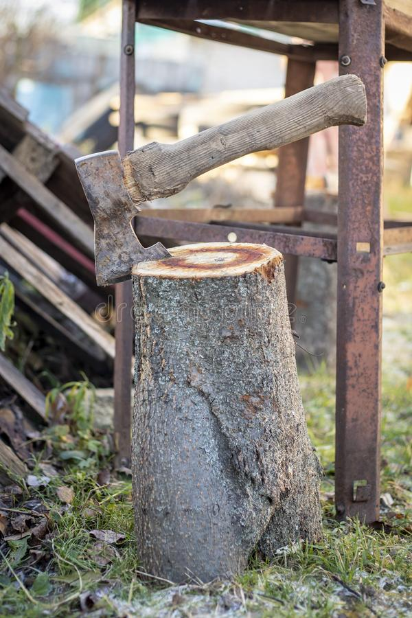 Old rusty ax stuck in a wooden stump royalty free stock photography